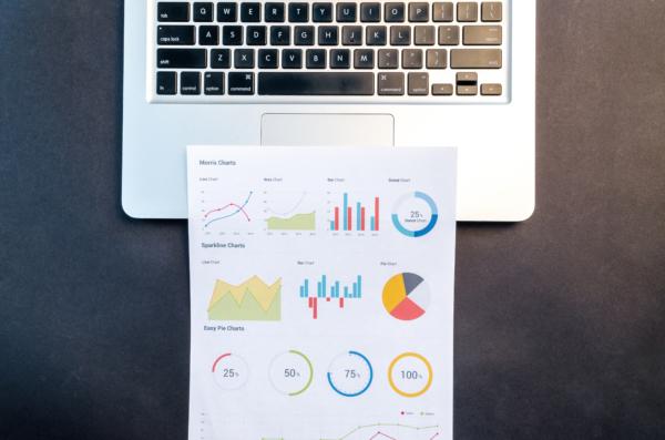 Teclado de um notebook com uma página de relatório impressa